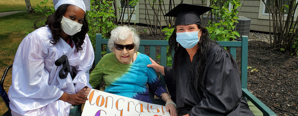 Resident holding Congrats Grads sign with two graduates